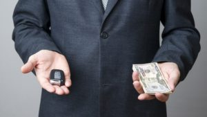 businessman-offering-car-key-money